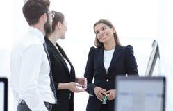 Affärslag som talar det stående near skrivbordet Arkivbild