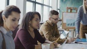 Affärslagmöte på det moderna kontoret Idérik ung grupp människor för blandat lopp som diskuterar nya idéer med chefen lager videofilmer