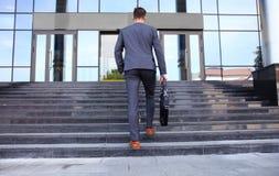 Affärsledare med portföljen som upp går trappan Arkivfoton