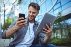 Affärsledare som använder mobiltelefonen och den digitala minnestavlan Royaltyfri Bild