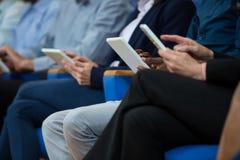 Affärsledare som deltar i ett affärsmöte genom att använda den digitala minnestavlan Arkivbild