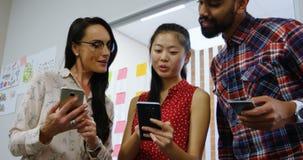 Affärsledare som diskuterar över en mobiltelefon 4k arkivfilmer