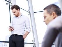 Affärsledare som i regeringsställning använder mobiltelefonen Royaltyfria Bilder