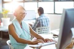 Affärsledare som lyssnar till musik, medan arbeta på datoren royaltyfri fotografi