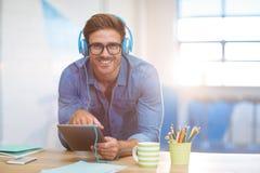 Affärsledare som lyssnar till musik på den digitala minnestavlan royaltyfri foto