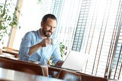 Affärslivsstil Affärsman som sitter på kafét som bläddrar materiel på bärbara datorn som dricker gladlynt kaffe royaltyfri bild