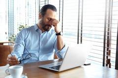 Affärslivsstil Affärsmannen som sitter på kafét med kaffe och bärbara datorn, stängde ögon som masserar den trötta näsbron royaltyfria bilder