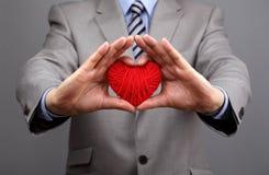 Affärsmän är hållande ut en röd hjärta Fotografering för Bildbyråer