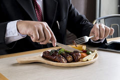 Affärsmän äter biff Fotografering för Bildbyråer