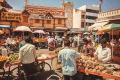 Affärsmän av ananors och tropiska frukter som talar med kunder på gatamarknaden Arkivfoto