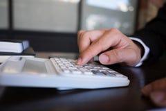 Affärsmän beräknar inkomsten från exportaffären på den wood tabellen äganderätt för home tangent för affärsidé som guld- ner skye arkivbild