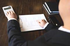 Affärsmän beräknar inkomsten från exportaffären på den wood tabellen äganderätt för home tangent för affärsidé som guld- ner skye royaltyfria foton