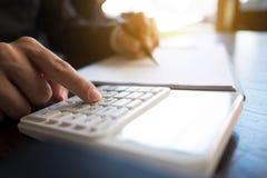 Affärsmän beräknar inkomsten från exportaffären på den wood tabellen äganderätt för home tangent för affärsidé som guld- ner skye arkivfoton