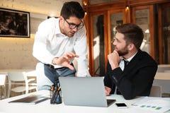 Affärsmän diskuterar företags mål framme av bärbara datorer på workp Royaltyfria Foton