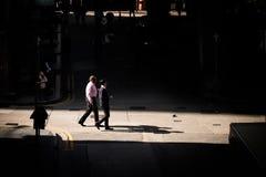 Affärsmän går över en liten föreningspunkt i den tillbaka gränden av Hong Kong arkivbilder