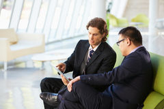 Affärsmän med Digital Tabletsammanträde i modernt kontor Arkivbild