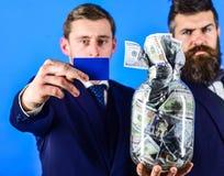 Affärsmän med kruset som är full av kassa och kreditkorten, blå bakgrund, slut upp, kopieringsutrymme Bankir finanschef royaltyfri fotografi