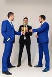 Affärsmän med lyckliga framsidor i formella dräkter rymmer det guld- priset royaltyfria bilder