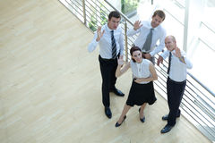 Affärsmän och kvinnaanseendet vid räcket med händer lyftte, ståenden Royaltyfri Fotografi