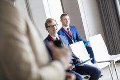 Affärsmän och offentlig högtalare i seminariumkorridor arkivfoto