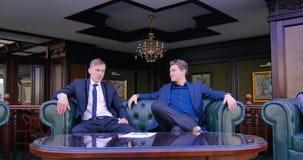 Affärsmän skakar händer, sitter på en läderstol och börjar att diskutera underteckningen av avtalet Direktör patos stock video
