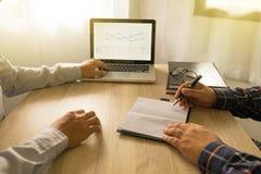 Affärsmän som använder bärbara datorn till läget på marknadsvärdet på M arkivfoton