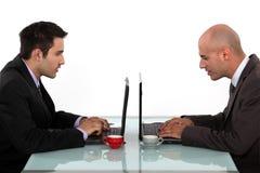 Affärsmän som arbetar på deras bärbara datorer Arkivfoto