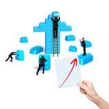 Affärsmän som bygger buntkvarter i övre form för pil arkivbilder