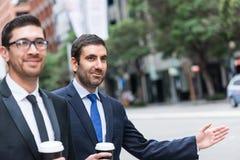 Affärsmän som fångar taxien royaltyfria foton
