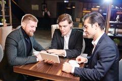Affärsmän som håller ögonen på presentation på kaffeavbrottet royaltyfri fotografi