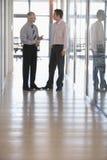 Affärsmän som har en diskussion i korridor arkivfoton