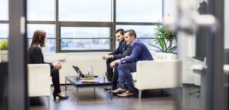 Affärsmän som intervjuar den kvinnliga kandidaten för jobb i modernt företags kontor royaltyfria bilder