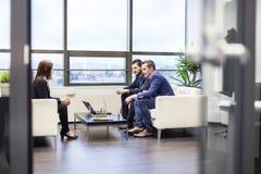Affärsmän som intervjuar den kvinnliga kandidaten för jobb i modernt företags kontor Arkivbilder