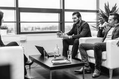 Affärsmän som intervjuar den kvinnliga kandidaten för jobb i modernt företags kontor Arkivbild