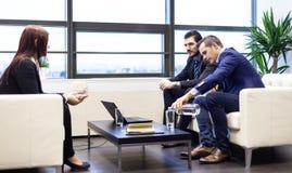 Affärsmän som intervjuar den kvinnliga kandidaten för jobb i modernt företags kontor Royaltyfri Fotografi