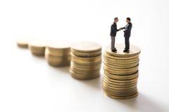 Affärsmän som kontrollerar handen över myntbuntar Arkivbild
