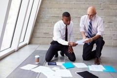 Affärsmän som lägger dokument på golv till planprojektet royaltyfri bild