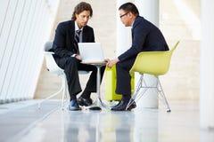 Affärsmän som möter bärbar dator i modernt kontor Arkivbild