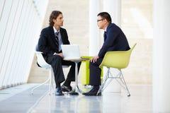 Affärsmän som möter bärbar dator i modernt kontor Royaltyfri Bild