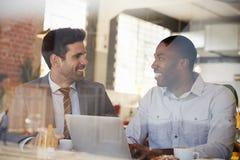 Affärsmän som möter i coffee shop som skjutas till och med fönster royaltyfria foton