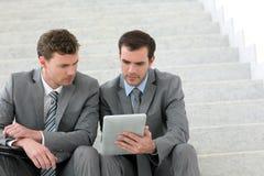 Affärsmän som möter på trappa genom att använda minnestavlan royaltyfri bild