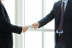 Affärsmän som passerar pengar Royaltyfria Foton