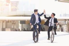 Affärsmän som rider cyklar arkivbild