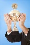 affärsmän som rymmer den höga trofén Arkivfoto