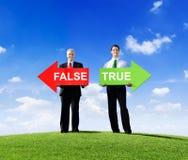 Affärsmän som rymmer pilar för falskt och riktigt royaltyfri bild