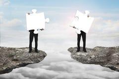 Affärsmän som rymmer pussel för att förbinda på klippan med clou Royaltyfria Foton