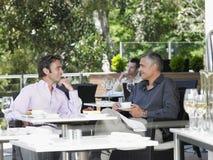 Affärsmän som samtalar på det utomhus- kafét arkivfoton