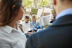 Affärsmän som sitter utanför att arbeta tillsammans på bärbara datorn royaltyfri bild