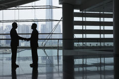 Affärsmän som skakar händer i flygplatsterminal Arkivfoto