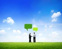 Affärsmän som skakar händer med anförandebubblan Arkivfoto